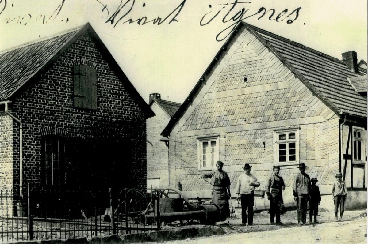 Schmiedemeister Heinrich Jürgens (links) vor seiner 1909 erbauten Schmiede und dem 1909 erworbenen Wohnhaus. Neben ihm stehen Schustern Heinrich Voß, Lehrling Rudolf Babilon, Johannes Theune mit zwei Söhnen