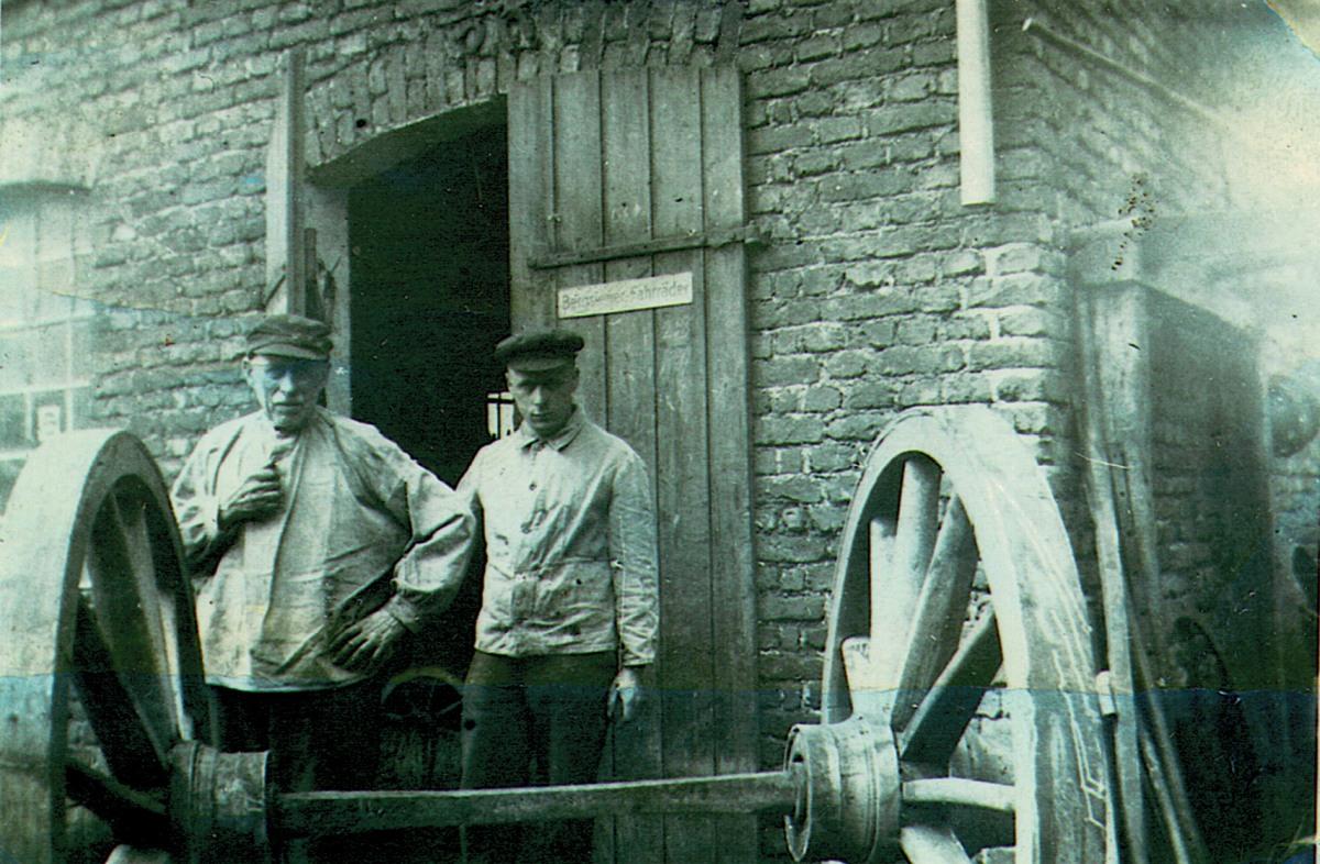 Die beiden Huf- und Wagenschmiedemeister Heinrich und Georg Jürgens vor der Werkstatt hinter einem Wagenteil (Hinterachse mit Holzrädern, auf die Eisenreifen aufgezogen worden sind). Aufnahme 1936