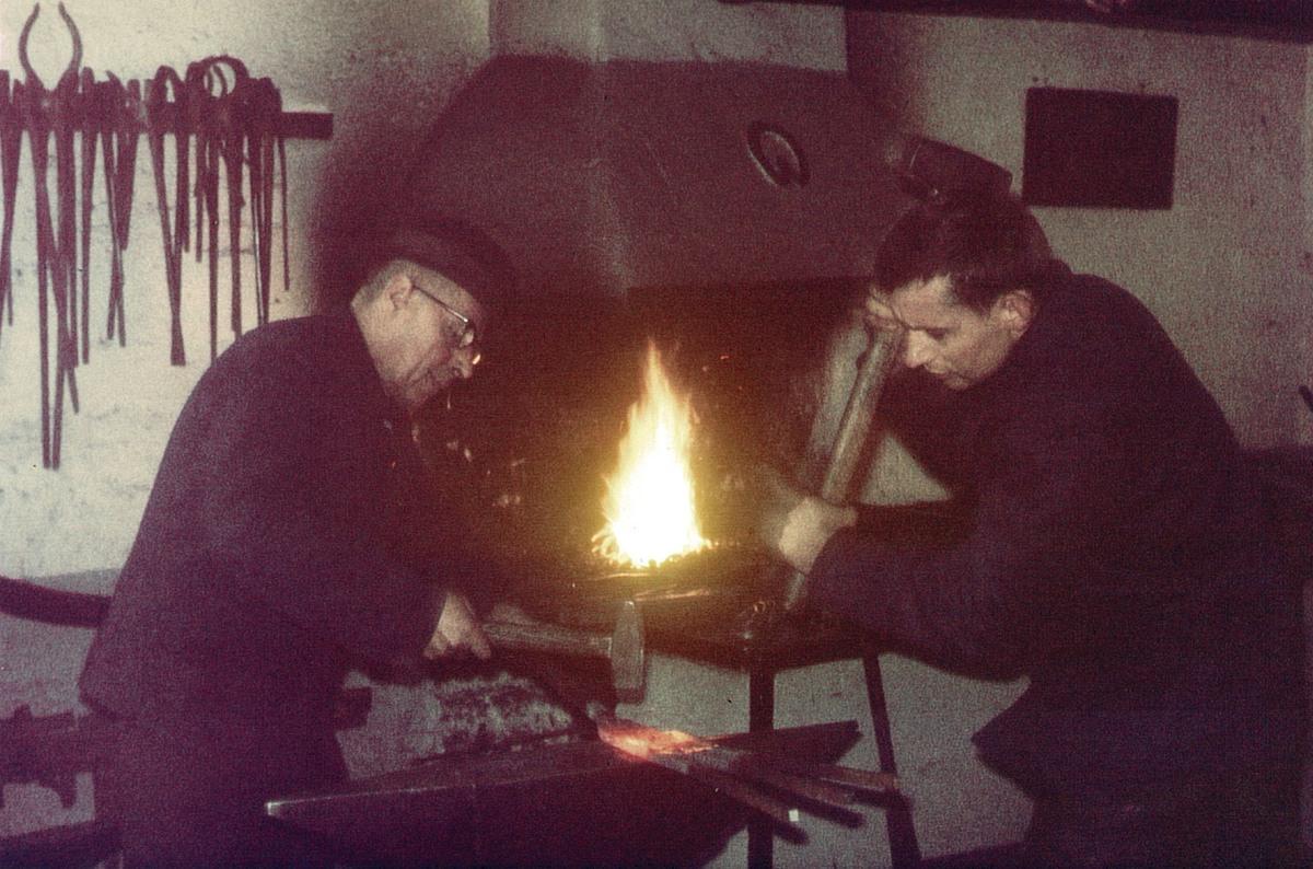 Meister Georg Jürgens und Geselle Heinrich Jürgens beim Kunstschmieden eines Zaunes in der umgebauten Werkstatt. Aufnahme 1966